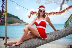 Mujer rubia linda en vestido, gafas de sol rojas y el sombrero de santa que se sienta en la palmera en la playa tropical exótica  Imágenes de archivo libres de regalías