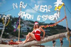 Mujer rubia linda en vestido, gafas de sol rojas y el sombrero de santa que se sienta en la palmera en la playa tropical exótica  Fotos de archivo