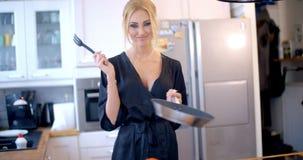Mujer rubia linda que cocina en la cocina almacen de metraje de vídeo