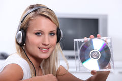 Mujer rubia listeing a la música Foto de archivo libre de regalías