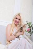 Mujer rubia lujosa en un vestido blanco con un perro pekingese Imagenes de archivo