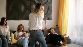 Mujer rubia magnífica en vaqueros y camisa que baila atractivo delante de sus novias Las muchachas se están sentando en un sofá metrajes