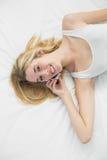Mujer rubia magnífica que llama por teléfono con su smartphone que sonríe en la cámara Fotografía de archivo