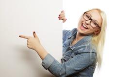 Mujer rubia magnífica que señala en un tablero mientras que se opone a Imágenes de archivo libres de regalías