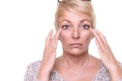 Mujer rubia mayor atractiva que comprueba su tez Imagen de archivo libre de regalías