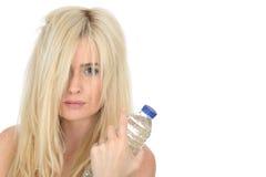 Mujer rubia natural joven sana apta que sostiene una botella de agua mineral Imagen de archivo libre de regalías