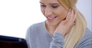 Mujer rubia ocupada con ella dispositivo de la tableta almacen de video