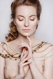 Mujer rubia oscura hermosa joven en un collar del oro Fotos de archivo