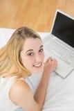 Mujer rubia pacífica que trabaja con su cuaderno que miente en su cama Foto de archivo