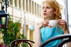 Mujer rubia pensativa en el café que sostiene la taza de café Imagen de archivo libre de regalías