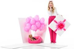 Mujer rubia por la caja de regalo con el perro del yorkie y los globos rosados Imagenes de archivo