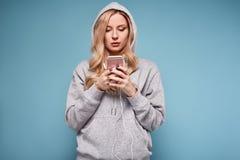 Mujer rubia positiva linda en música que escucha de la sudadera con capucha Fotografía de archivo libre de regalías