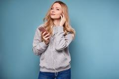 Mujer rubia positiva linda en música que escucha de la sudadera con capucha Imágenes de archivo libres de regalías