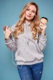 Mujer rubia positiva linda en sudadera con capucha con el teléfono y el café Foto de archivo libre de regalías