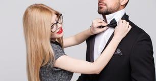 Mujer rubia que ajusta el arco del lazo según hombre en el smoking imágenes de archivo libres de regalías