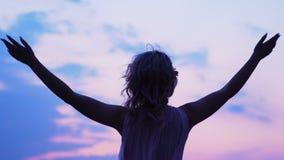 Mujer rubia que aumenta las manos que miran el cielo, sensación de la libertad, éxito, sueños metrajes