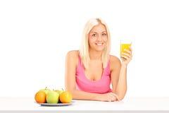 Mujer rubia que bebe un zumo de naranja asentado en la tabla Fotos de archivo libres de regalías