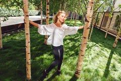 Mujer rubia que camina cerca de árboles de abedul el día de verano Fotos de archivo