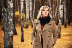 Mujer rubia que camina en bosque del otoño Imagenes de archivo