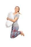 Mujer rubia que celebra una almohada y un salto Foto de archivo libre de regalías