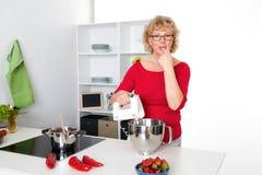 Mujer rubia que cocina y que cuece en la cocina Fotos de archivo