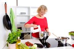 Mujer rubia que cocina y que cuece en la cocina Imagen de archivo libre de regalías