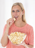 Mujer rubia que come las palomitas Imagen de archivo libre de regalías