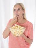 Mujer rubia que come las palomitas Fotos de archivo