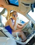 Mujer rubia que conduce y que habla con el teléfono móvil Fotos de archivo