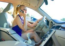 Mujer rubia que conduce y que habla con el teléfono móvil Foto de archivo libre de regalías