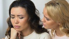 Mujer rubia que conforta y que apoya a su compañero de cuarto asiático triste, amistad de las muchachas almacen de video