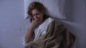 Mujer rubia que despierta en la náusea de la sensación de la mañana, náuseas matinales, top-vista almacen de video