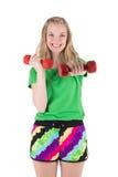 Mujer rubia que ejercita con pesas de gimnasia rojas Imagen de archivo libre de regalías