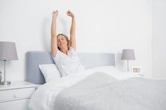 Mujer rubia que estira sus brazos en cama por la mañana Foto de archivo