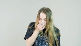 Mujer rubia que estornuda en el fondo blanco metrajes