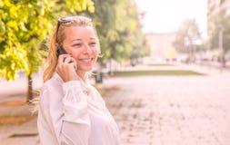 Mujer rubia que habla en el teléfono Foto de archivo libre de regalías