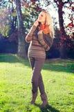 Mujer rubia que habla y que camina en un parque Imágenes de archivo libres de regalías