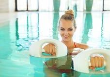 Mujer rubia que hace aeróbicos de la aguamarina con pesas de gimnasia de la espuma en la natación Fotos de archivo