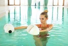 Mujer rubia que hace aeróbicos de la aguamarina con pesas de gimnasia de la espuma en la natación Imágenes de archivo libres de regalías