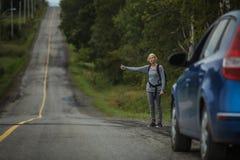 Mujer rubia que hace autostop en el lado del camino Foto de archivo libre de regalías
