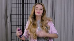 Mujer rubia que hace su pelo spritz la laca metrajes