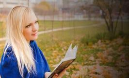 Mujer rubia que lee un libro en el parque del otoño Fotos de archivo libres de regalías