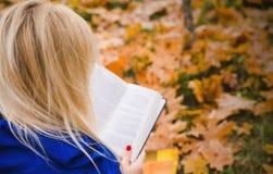 Mujer rubia que lee un libro en el parque del otoño Fotos de archivo