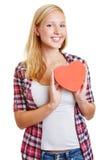 Mujer rubia que lleva a cabo el corazón rojo Foto de archivo libre de regalías