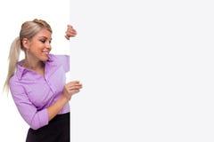 Mujer rubia que lleva a cabo a la cara de una tarjeta en blanco de la muestra Fotografía de archivo libre de regalías