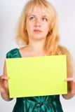 Mujer rubia que lleva a cabo un espacio en blanco Fotos de archivo libres de regalías