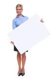 Mujer rubia que lleva a cabo una tarjeta de mensaje en blanco. Fotografía de archivo