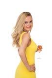 Mujer rubia que lleva el champán de consumición del vestido amarillo Fotos de archivo libres de regalías