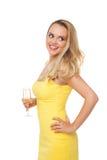 Mujer rubia que lleva el champán de consumición del vestido amarillo Fotografía de archivo libre de regalías