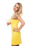 Mujer rubia que lleva el champán de consumición del vestido amarillo Imagenes de archivo